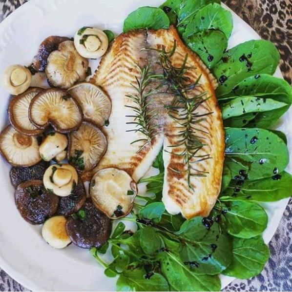 Filé de tilápia grelhada com mix de cogumelos, salada de rúcula e pesto de agrião